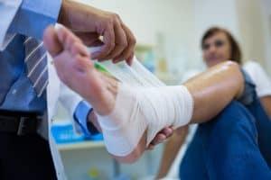 רופא חובש כף רגל של מטופלת שאיבדה את כושר העבודה שלה
